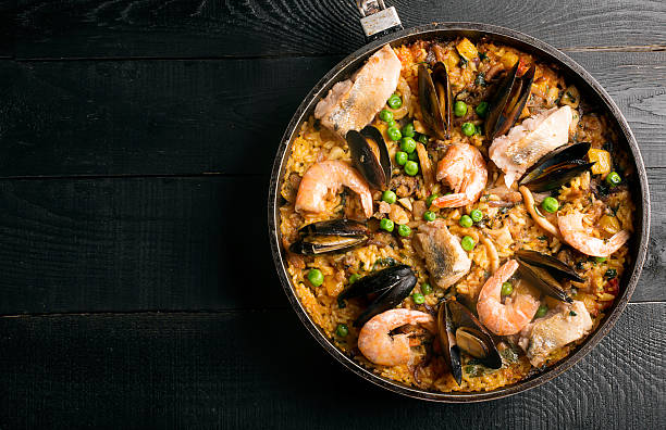 traditional seafood paella in the pan - paella stock photos and pictures