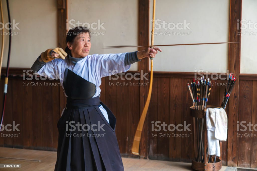 Traditional Senior archer looses an arrow from her bow stock photo