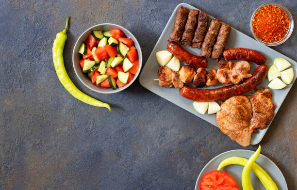 traditional serbian and balkan grilled meat called mesano meso. balkan barbeque (rostilj) served with serbian salad, hot peppers, bread, tomato, onions, and paprika powder. dark background. top view - serbia stock photos and pictures