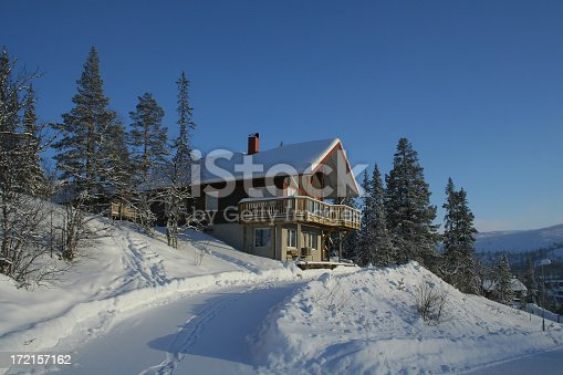 A traditional wooden chalet surrounded by deep snow on a blue sky day.