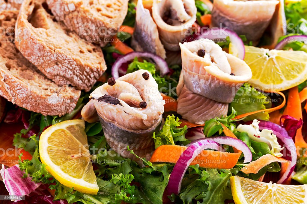 Traditional snacks salted herring with vegetables, onion, lemon, yellow lime royalty-free stock photo