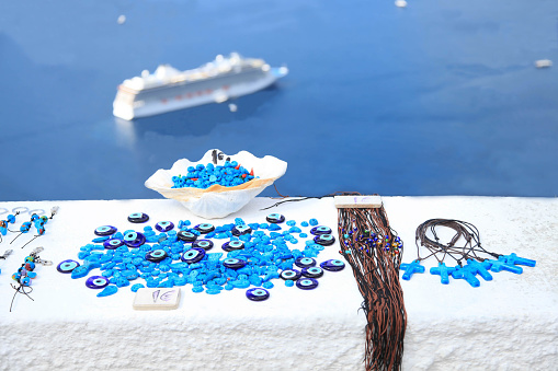Traditional souvenirs in Oia, in Santorini, Greece. Ship and sea on background of picture