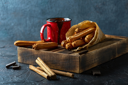 Churros in paper bag and mug of hot chocolate on a wooden tray on textured dark background, selective focus.