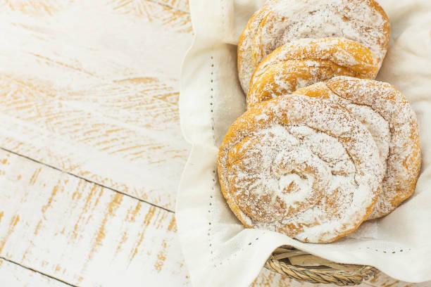 traditionelle spanische oder philippinischen gebäck ensaimada. in pulverform in weidenkorb. weißer holztisch. gemütliche rustikale küche - typisch 90er stock-fotos und bilder