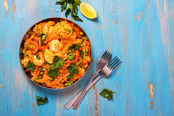 traditional spanish paella dish with seafood, peas, rice and chicken - paella stock photos and pictures