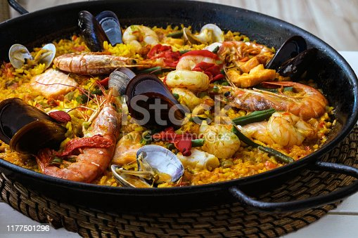 Traditional spanish seafood paella dish in a black pan. Mussels, Amandi and prawns on a pillow of rice. Close-up. Delicious wholesome dinner in a Spanish restaurant on the island of Mallorca.