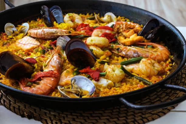 traditionele spaanse zeevruchten paella schotel in een zwarte pan. mosselen, amandi en garnalen op een kussen van rijst. close-up. heerlijk gezond diner in een spaans restaurant op het eiland majorca. - paella stockfoto's en -beelden