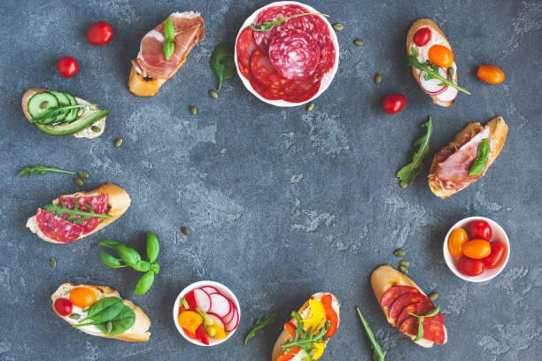 traditionelle spanische tapas auf dunklem hintergrund. flach legen, top aussicht - salami vorspeise stock-fotos und bilder