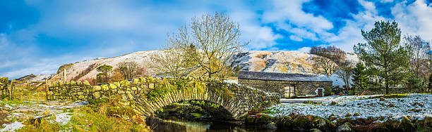 Traditional stone bridge over mountain stream snowy Lake District Cumbria Traditional arch bridge and dry stone walls overlooked by the snow dusted summits of the Eastern Fells of the Lake District National Park, Cumbria. high seat stock pictures, royalty-free photos & images