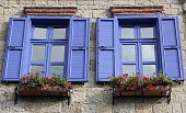 Traditional Stone Facade View. Blue frame windows with flower pots.