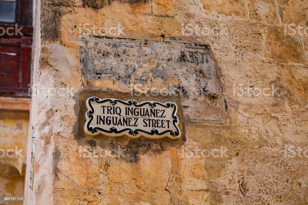 MDINA, MALTA - OCTOBER 15, 2016: Traditional street sign in the old town that was founded as Maleth in around the 8th century BC by Phoenician settlers on the island of Malta stock photo