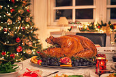 Table is set up for celebrating Christmas. On the table is a traditional stuffed roasted turkey with side dishes and Christmas decoration