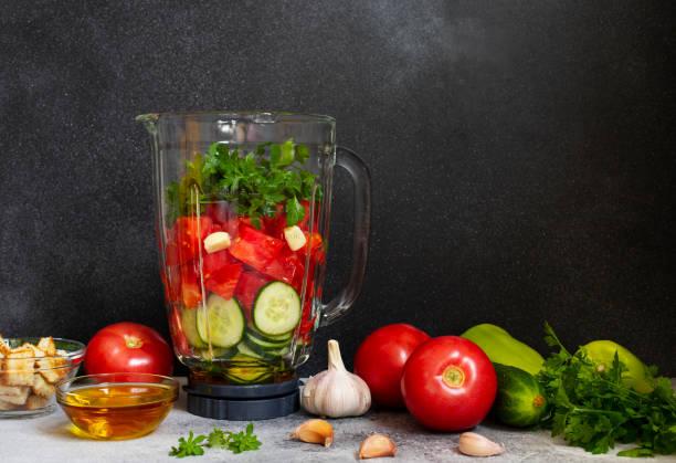 traditionelle sommerliche tomatensuppe gazpacho zutaten in einem mixer. tomaten, pfeffer, knoblauch, basilikum, petersilie, olivenöl und croutons. mediterrane, spanische küche. schwarzer hintergrund. kopierplatz - kalte tomatensuppe stock-fotos und bilder
