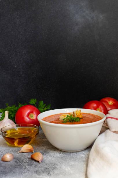 traditionelle sommerkälte tomatensuppe gazpacho. tomaten, knoblauch, basilikum, petersilie, olivenöl und croutons. mediterrane, spanische küche. nahaufnahme. schwarzer hintergrund. platz kopieren. senkrecht - kalte tomatensuppe stock-fotos und bilder