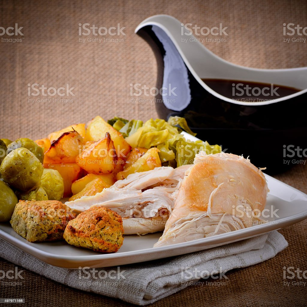 Traditional Sunday dinner with gravy boat. stock photo