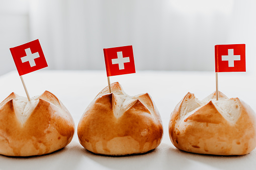 Traditional swiss bread buns called in German 1.Augustweggen baked in Switzerland to celebrate Swiss National Day on August 1st. The top of the bread being cut crosswise to shape a cross as symbol of Switzerland. Swiss flags on wooden toothpicks.  White background, isolated, copy space.