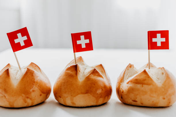 Traditional swiss bread buns called in German 1.Augustweggen baked in Switzerland to celebrate Swiss National Day on August 1st. The top of the bread being cut crosswise to shape a cross as symbol of Switzerland. Swiss flags on wooden toothpicks. Traditional swiss bread buns called in German 1.Augustweggen baked in Switzerland to celebrate Swiss National Day on August 1st. The top of the bread being cut crosswise to shape a cross as symbol of Switzerland. Swiss flags on wooden toothpicks.  White background, isolated, copy space. annually stock pictures, royalty-free photos & images