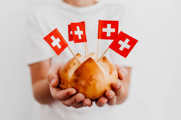 Traditional swiss bread buns called in German 1.Augustweggen baked in Switzerland to celebrate Swiss National Day on August 1st. Body parts, children hands holding bread. Swiss flags on wooden toothpicks. White background, isolated, copy space. Traditional swiss bread buns called in German 1.Augustweggen baked in Switzerland to celebrate Swiss National Day on August 1st. Body parts, children hands holding bread. Swiss flags on wooden toothpicks. White background, isolated, copy space. annually stock pictures, royalty-free photos & images
