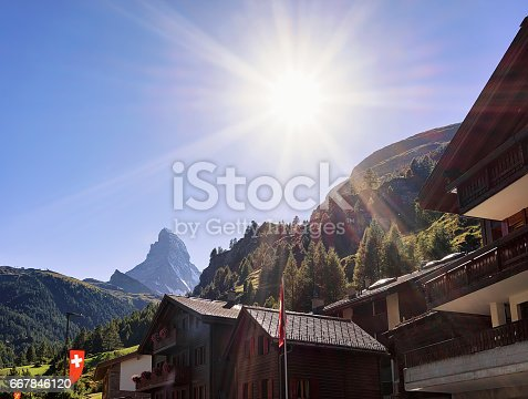 Traditional Swiss Chalets in Zermatt with Matterhorn summit with flags, Switzerland in summer.