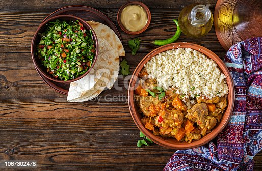 istock Traditional tajine dishes, couscous  and fresh salad  on rustic wooden table. Tagine lamb meat and pumpkin. Top view. Flat lay 1067302478