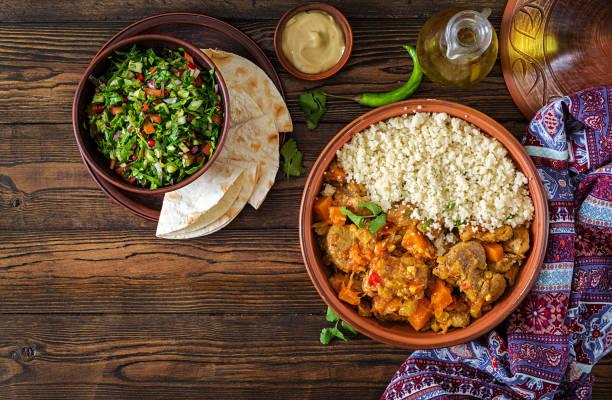 traditionelle tajine-gerichte, couscous und frischem salat auf rustikalen holztisch. tajine lammfleisch und kürbis. ansicht von oben. flach zu legen - safransauce stock-fotos und bilder