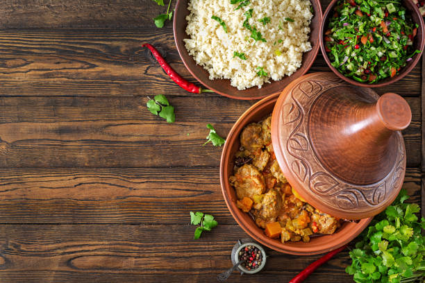 Traditional tajine dishes, couscous  and fresh salad  on rustic wooden table. Tagine lamb meat and pumpkin. Top view. Flat lay stock photo