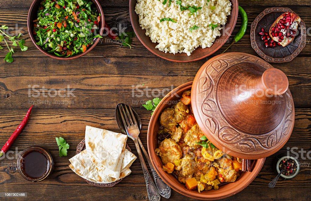Traditionelle Tajine-Gerichte, Couscous und frischem Salat auf rustikalen Holztisch. Tajine Lammfleisch und Kürbis. Ansicht von oben. Flach zu legen – Foto