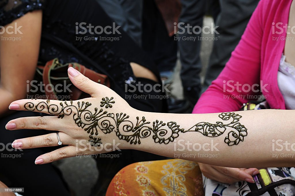 Traditional temporary tattoo on hand and arm - Stock image .