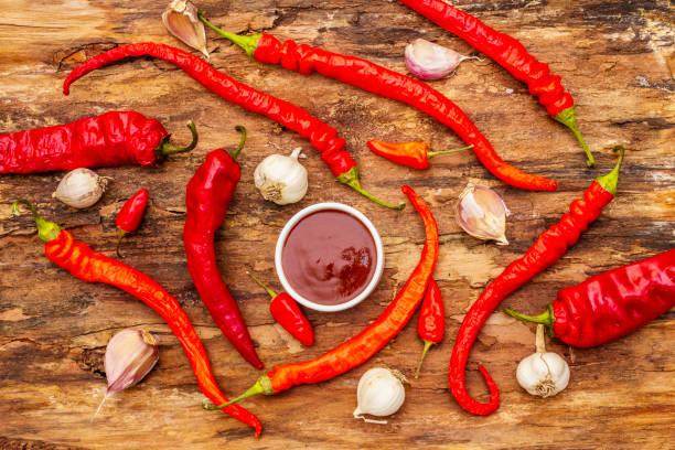 traditionelle thai-sauce sriracha mit zutaten. leicht getrocknete rote und orange chili, knoblauch - peperoni stiche stock-fotos und bilder