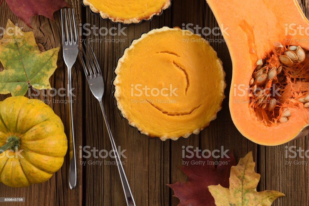 Traditional Thanksgiving dessert. Open pumpkin pie served with bright orange pumpkins and marple leaves on old wooden table stock photo