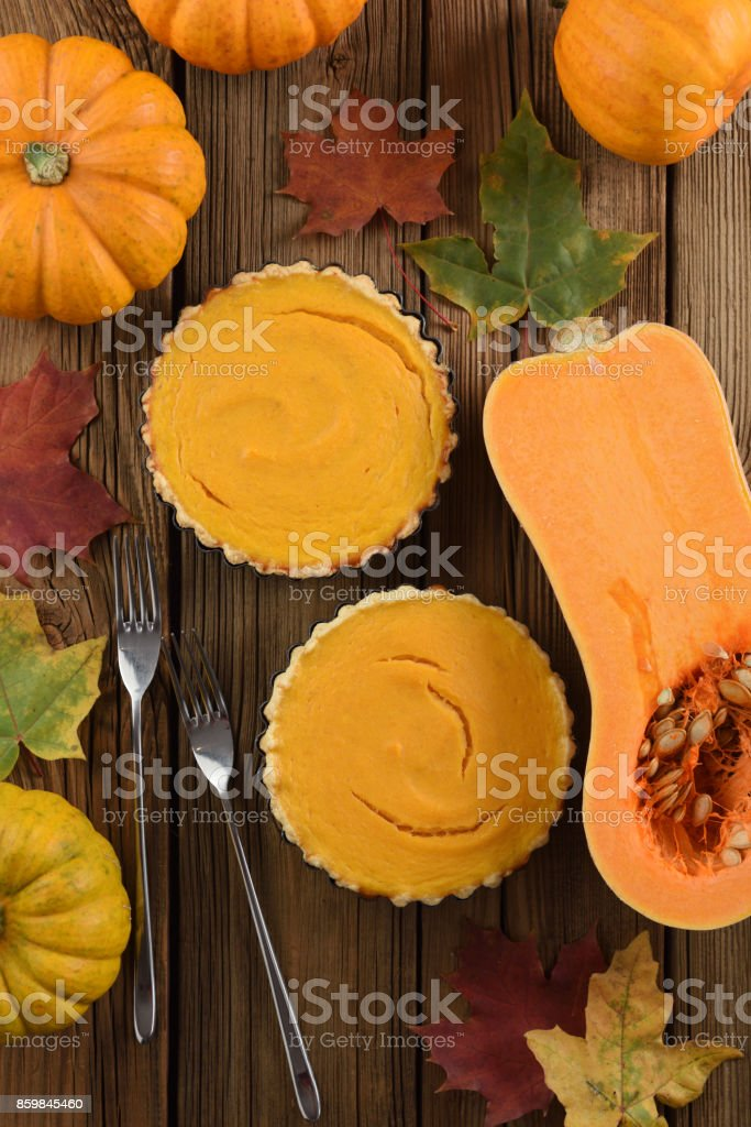 Traditional Thanksgiving dessert. Open pumpkin pies served with two forks, bright orange pumpkins and marple leaves on vintage wooden background stock photo