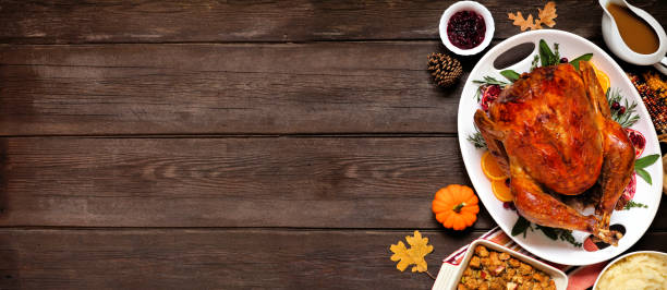 Traditional Thanksgiving turkey dinner. Overhead side border on a dark wood banner background. stock photo