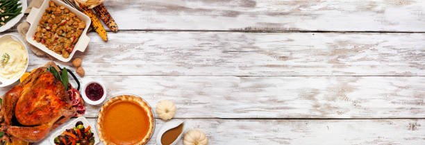 Traditional Thanksgiving turkey dinner. Top view corner border on a rustic white wood banner background. stock photo