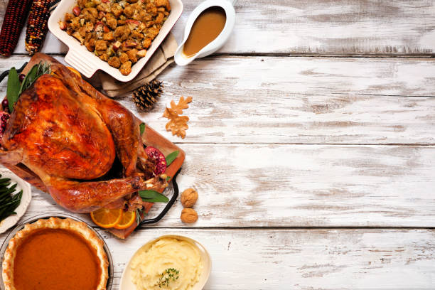 Traditional Thanksgiving turkey dinner. Top view side border on a rustic white wood background. stock photo