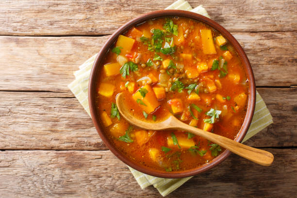 Traditional thick sweet potato soup with lentils close up in a bowl on the table. Horizontal top view Traditional thick sweet potato soup with lentils close up in a bowl on the table. Horizontal top view from above stew stock pictures, royalty-free photos & images