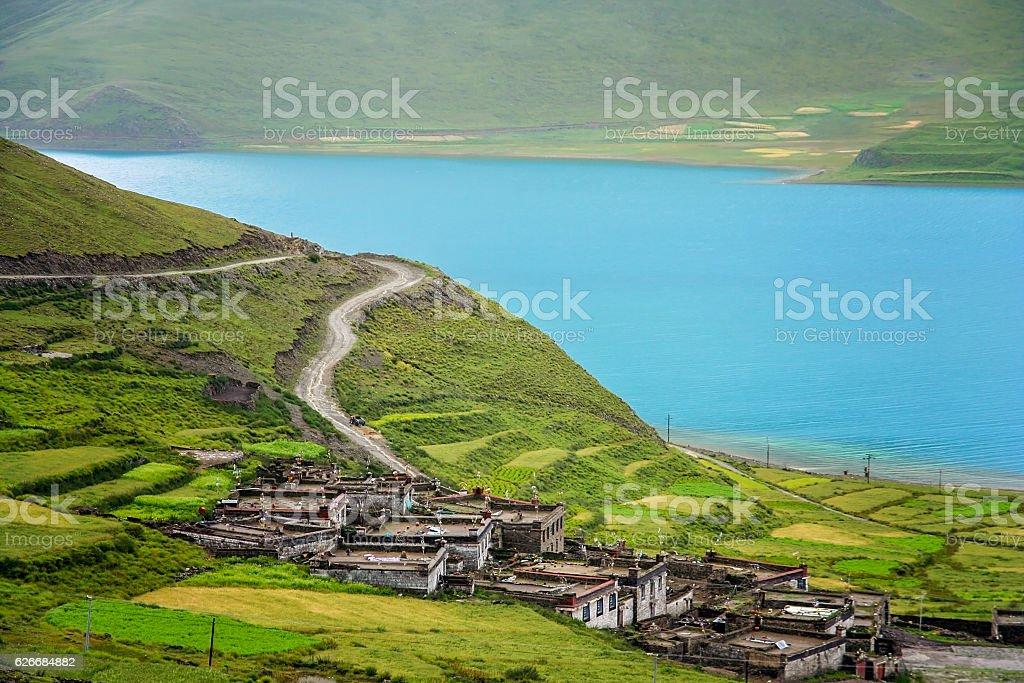 Traditional tibetan homes above Yamdrok Tso Lake lake stock photo