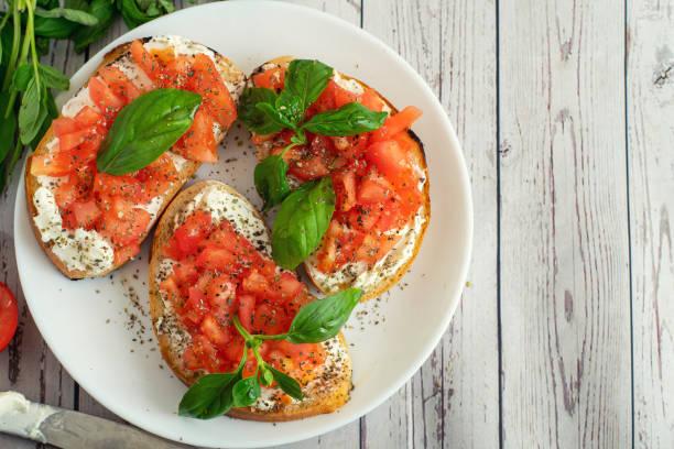 전통적인 이탈리아 토마토 브루 쉐 타와 밝은 나무 배경에 바질과 향신료를 구운. 상위 뷰 비스 복사 공간 - 브루스케타 뉴스 사진 이미지