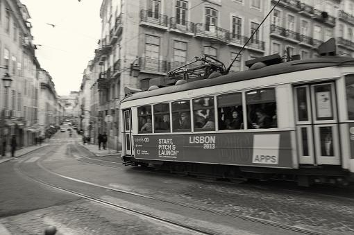 Lisbon, Portugal - April 7, 2013: A traditional tram runs along a street in Lisbon downtown.