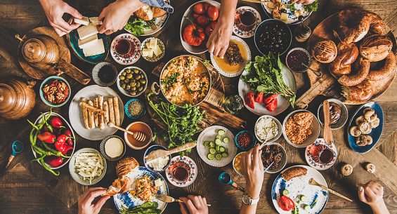Turkish breakfast table. Flat-lay of peoples hands taking pastries, vegetables, greens, olives, cheeses, fried eggs, spices, jams, honey, tea in copper pot and tulip glasses, wide composition