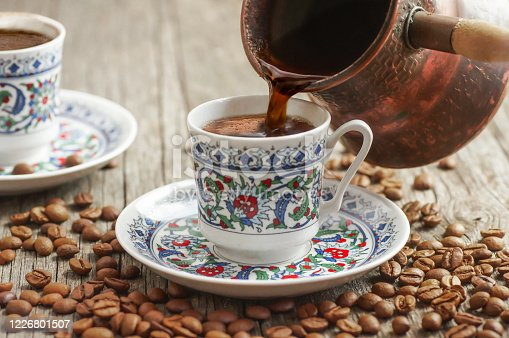 traditional turkish coffee in porcelain cup pouring from copper coffee pot, hot drink concept