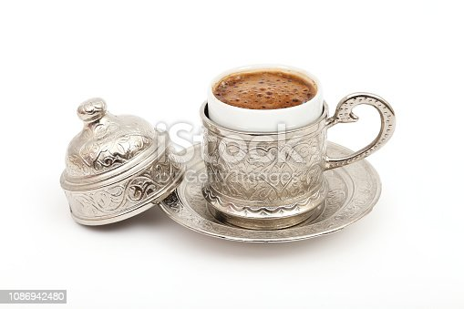 Turkish coffee in traditional silver cup on isolated white background