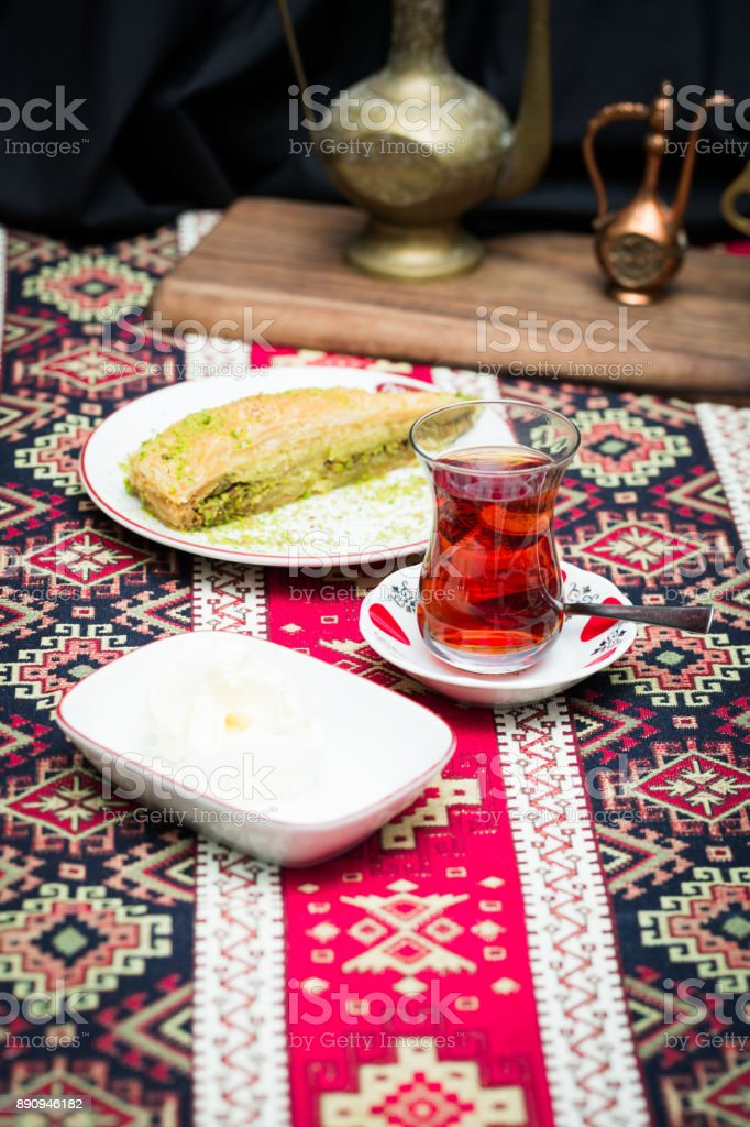 Traditional Turkish dessert baklawa with ice cream and pistachios and tea in pear shaped glass stock photo