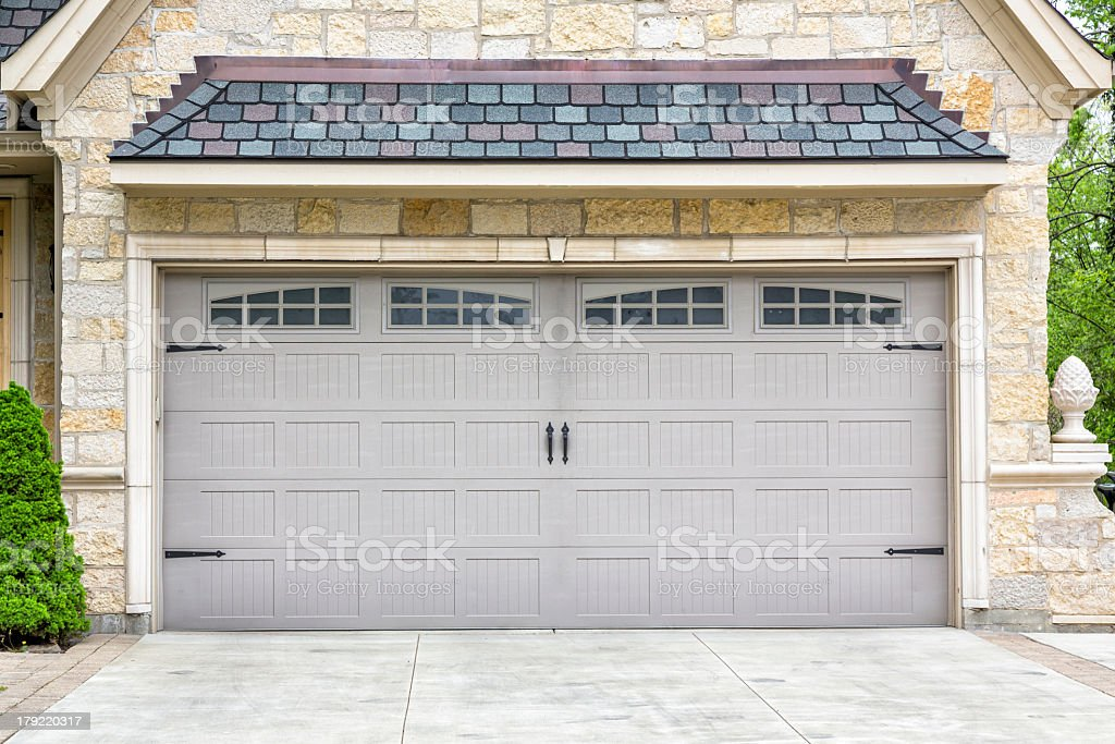 Traditional two car garage with windows and grey panels stock photo