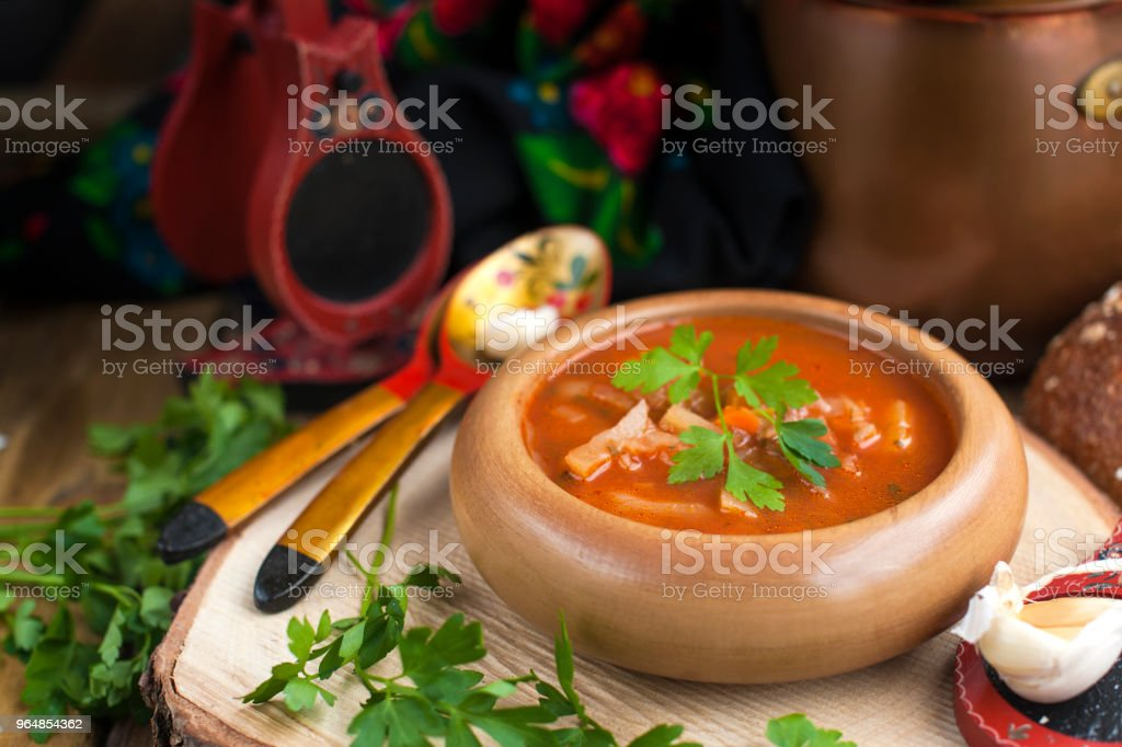 Traditional Ukrainian beet soup borscht in wooden bowl with garlic buns pampushka and dry cured pork belly on rustic wooden table royalty-free stock photo