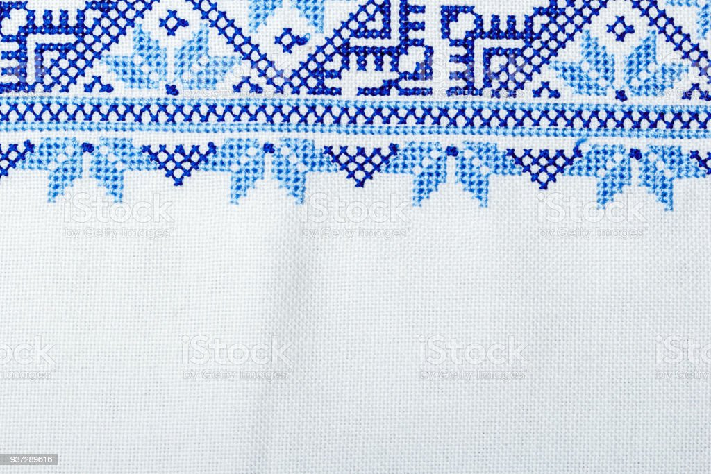 Traditional Ukrainian ornament embroidered with a cross on a linen cloth close-up. Copy space stock photo