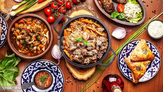 istock Traditional Uzbek oriental cuisine. Uzbek family table from different dishes for the New Year holiday. The background image is a top view. 1010677810
