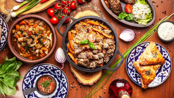 traditional uzbek oriental cuisine. uzbek family table from different dishes for the new year holiday. the background image is a top view. - christmas cooking imagens e fotografias de stock
