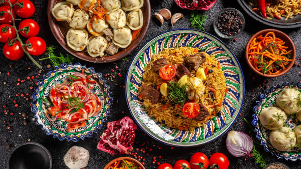 traditional uzbek oriental cuisine. uzbek family table from different dishes in national dishes for the new year holiday. the background image is a top view, copy space, flat lay - asia orientale foto e immagini stock
