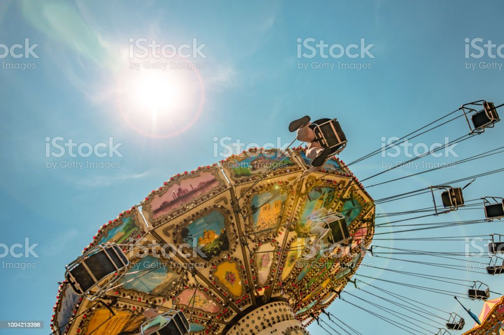 Traditional Victorian chair-o-plane ride with the sun stock photo