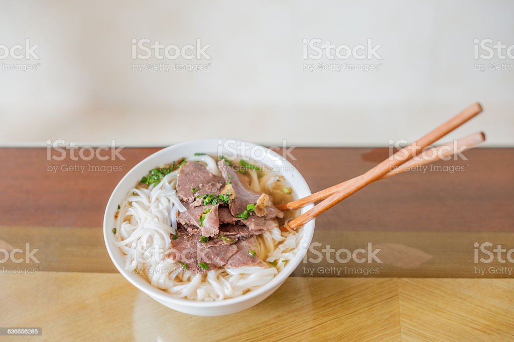 Traditional Vietnamese beef soup pho on a wooden background stock photo